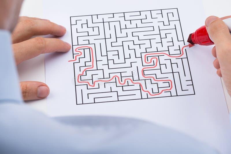Person Solving Maze Puzzle imagens de stock
