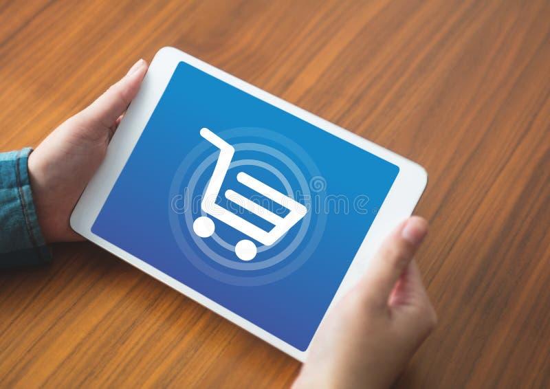 Person som använder minnestavlan med shoppingspårvagnsymbolen royaltyfria bilder