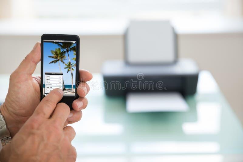 Person som använder mobiltelefonen för utskrift av fotoet royaltyfri bild