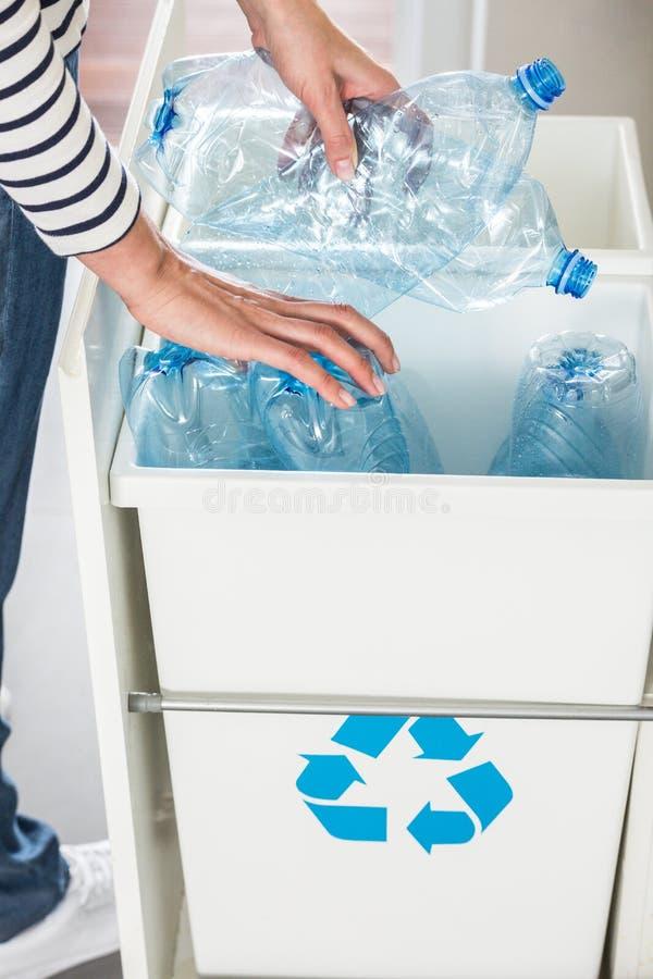 Person som avskiljer plast-flaskor arkivbild