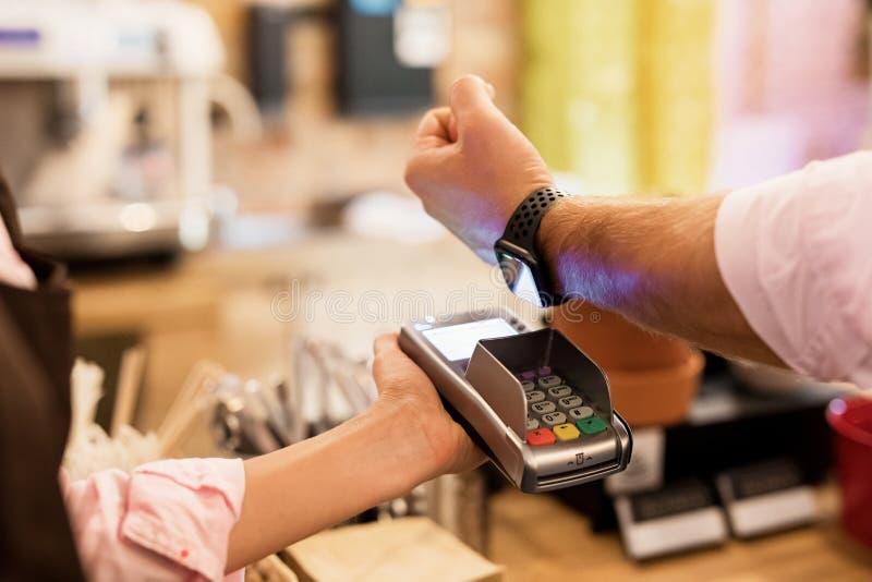Person som betalar på kafét med den smarta klockan wirelessly på pos.-terminalen royaltyfri bild