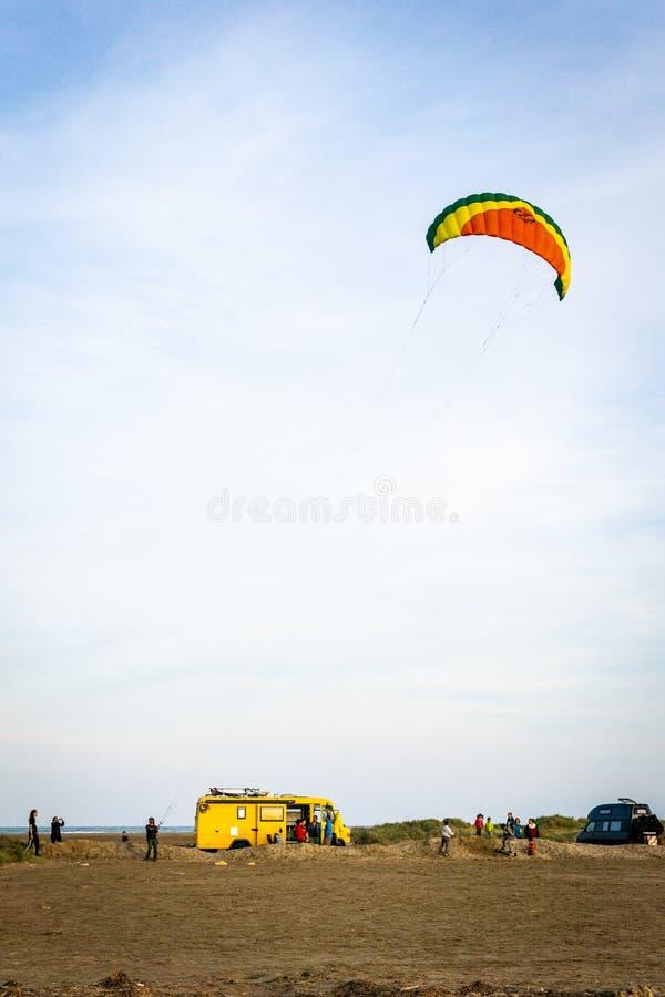 Person som flyger en bränningdrake på stranden med skåpbilar i bakgrunden royaltyfria foton