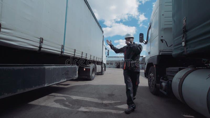 Person som går mellan två lastbilar arkivbilder
