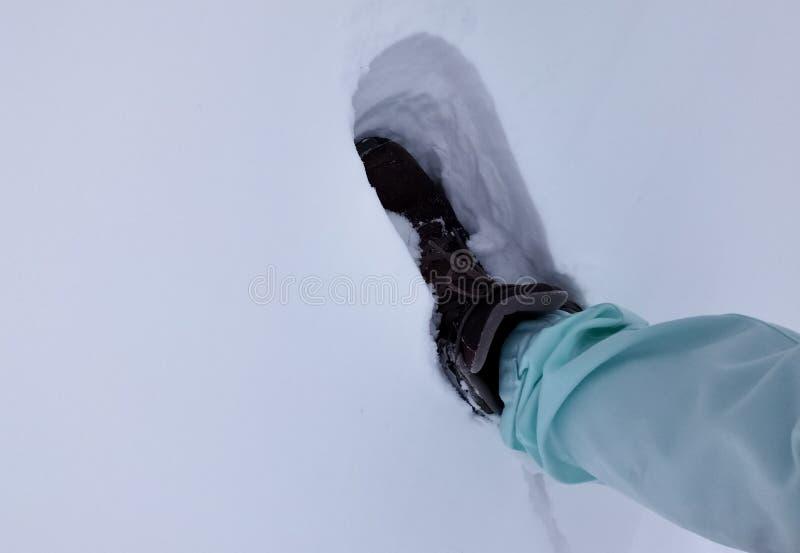 Person som går på snö med läderkängor, och vinter som cloathing royaltyfria bilder