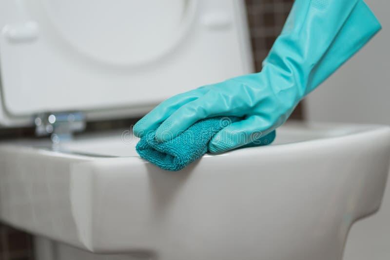 Person som gör ren toalettplatsen i rubber handskar arkivfoton