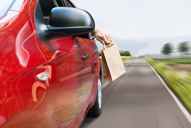 Person som kastar avfall ut ur bilfönster fotografering för bildbyråer