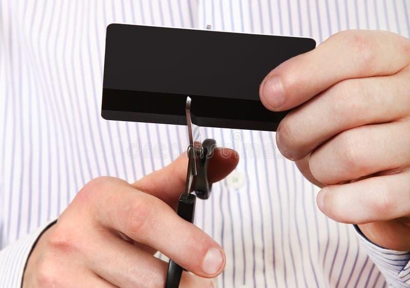 Person som klipper en kreditkort royaltyfria bilder