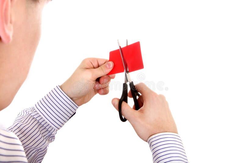 Person som klipper en kreditkort arkivfoton
