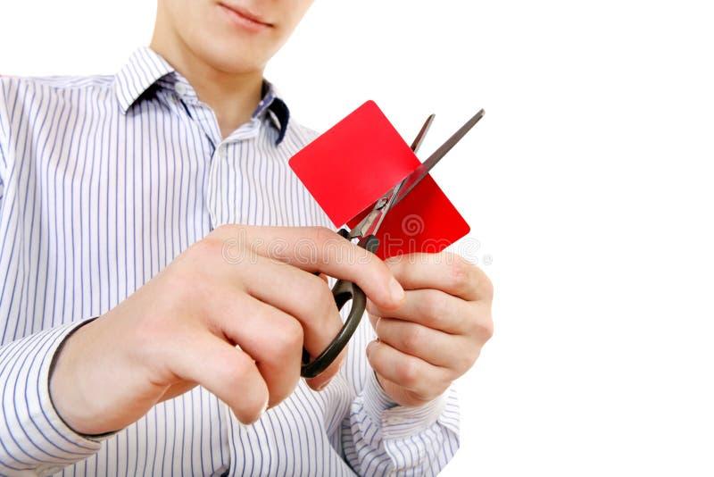 Person som klipper en kreditkort royaltyfri fotografi