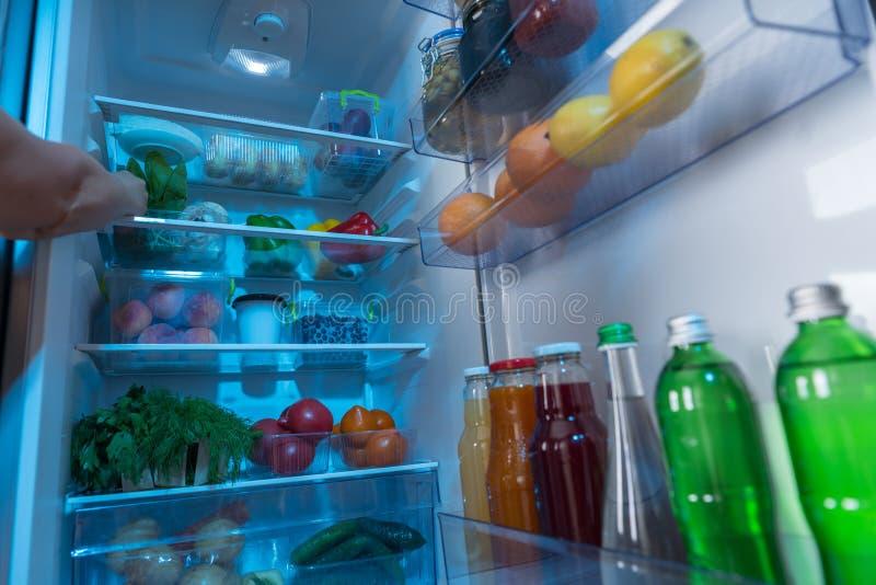 Person som når in i ett kylskåp för ny mat arkivbild