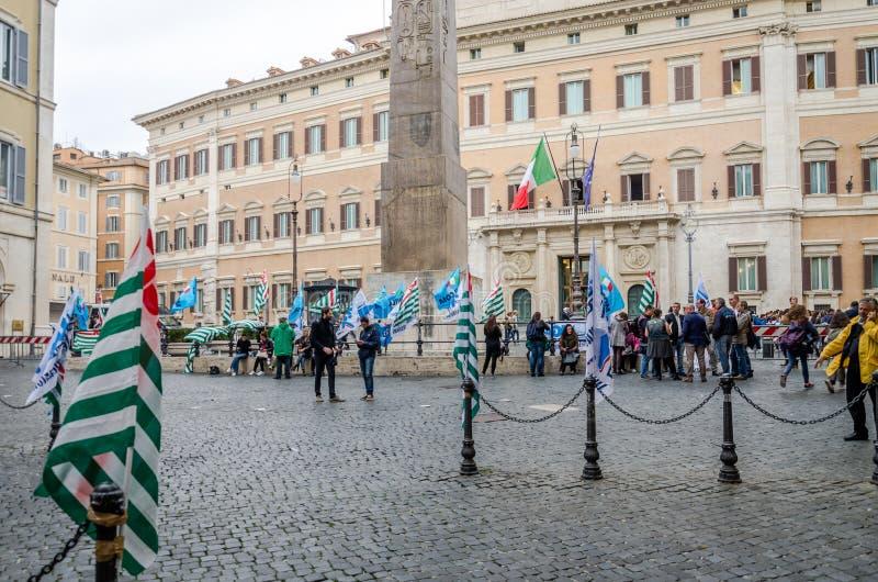 Person som protesterarfolk som samlas för att slå med flaggor som är främsta av den italienska regeringen i Rome royaltyfri foto