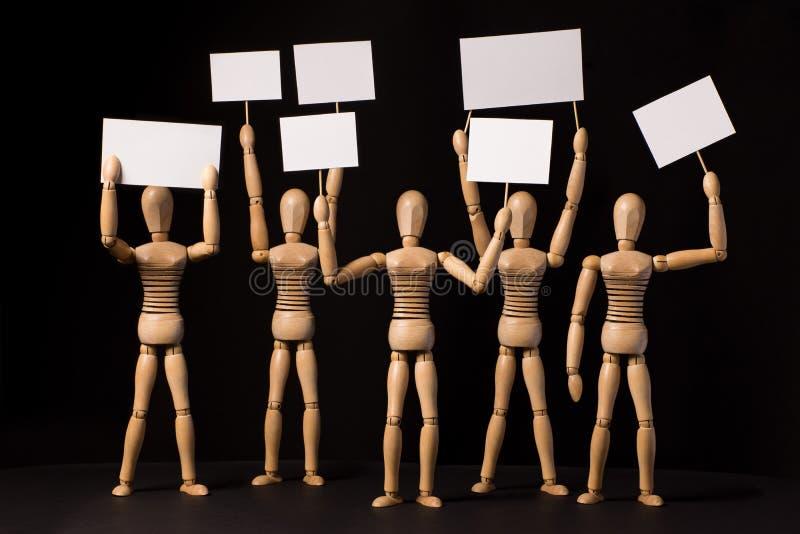 Person som protesterarträdockor med affischer eller baner i deras händer arkivfoton
