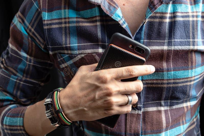 Person som rymmer en bärbar uppladdare med en smartphone i hans hand royaltyfri foto