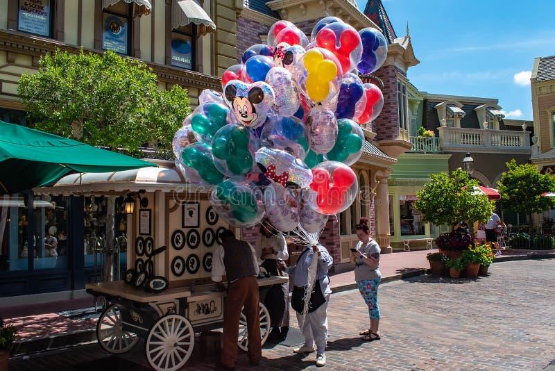Person som säljer färgrika Mickey ballonger i magiskt kungarike på Walt Disney World arkivbilder