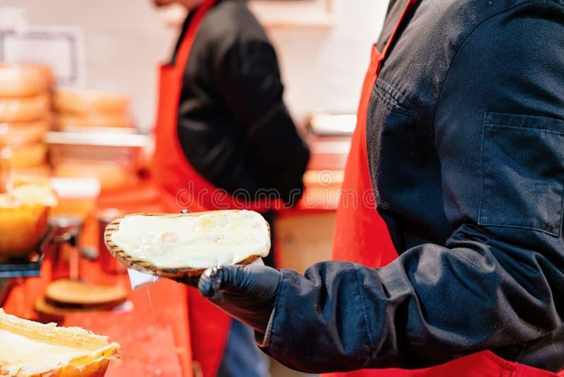 Person som säljer rostat brödbröd med racletteost royaltyfri foto