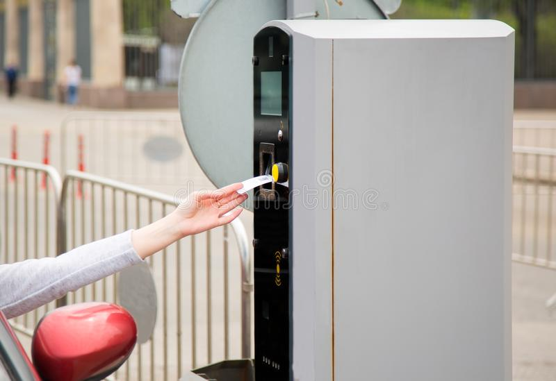 Person som sätter in in i eller tar bort biljetten från parkeringsmaskinen arkivfoto