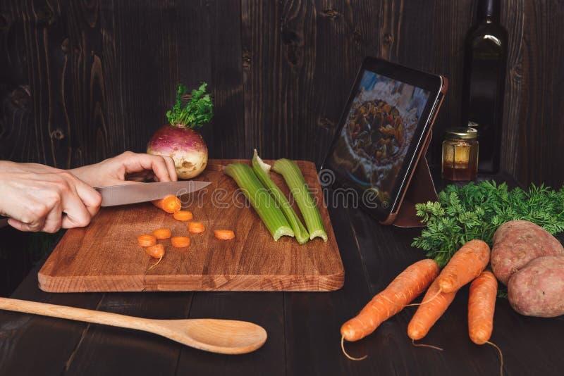 Person som ser den digitala minnestavlan och lagar mat sund mat i köket, bitande grönsaker på trätabellen arkivfoton