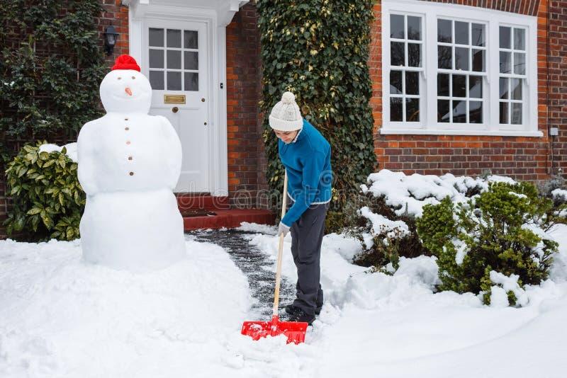 Person som skyfflar snow fotografering för bildbyråer