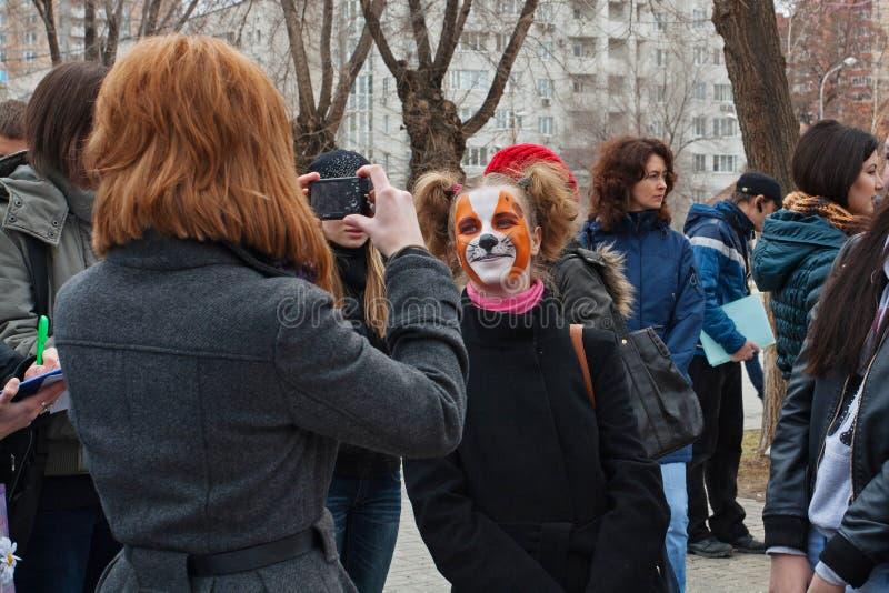 Person som tar en bild av flickan i makeup i internationell handling för skyddet av ` för djur`-rent spel i Volgograd arkivfoto