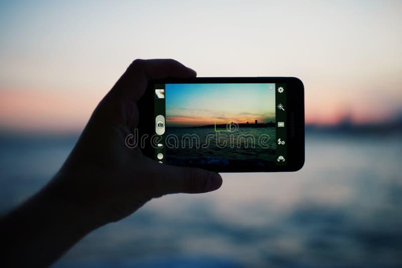 Person som tar ett foto av den fantastiska solnedgången genom att använda den smarta telefonkameran arkivbilder