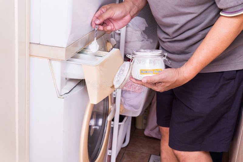 Person som tillfogar natriumbikarbonat in i tvagningmaskinen till washkläder arkivfoton