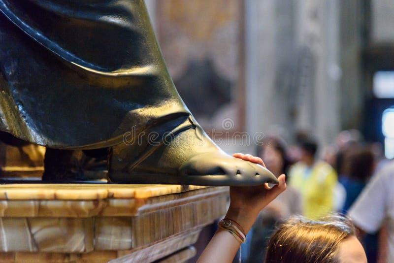 Person som trycker på foten av den St Peter statyn Inre av Sts Peter basilika i Vaticanen royaltyfria foton