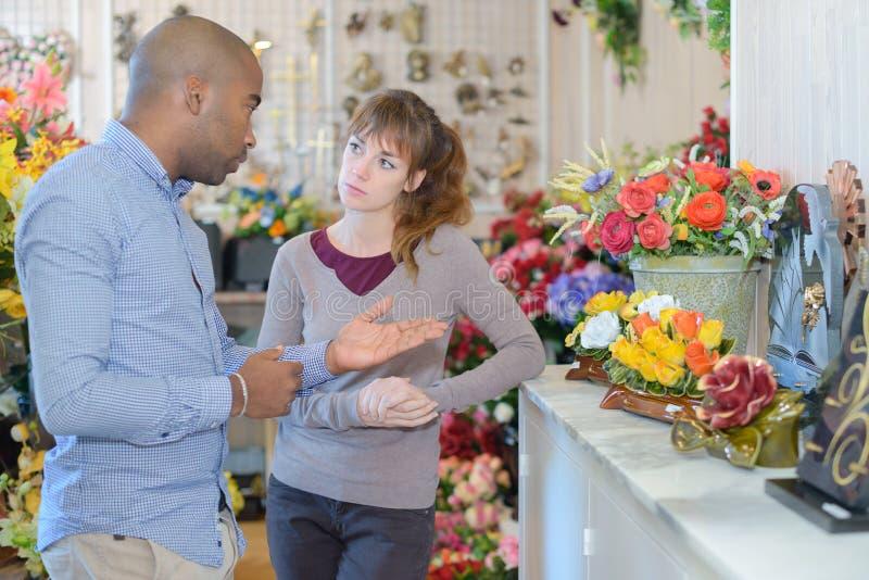 Person som v?ljer begravnings- blommor royaltyfri bild