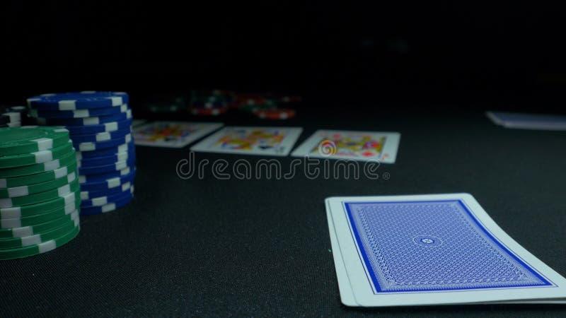 Person som visar hans däck på pokerleken Kortspelaren kontrollerar hans hand, två överdängare in, chiper i bakgrund på gräsplan arkivfoton