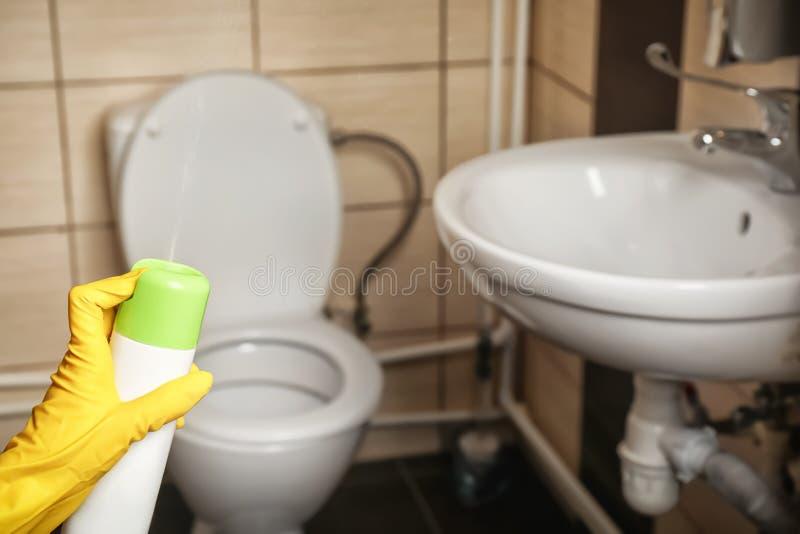 Person spraying air freshener. In bathroom royalty free stock photo