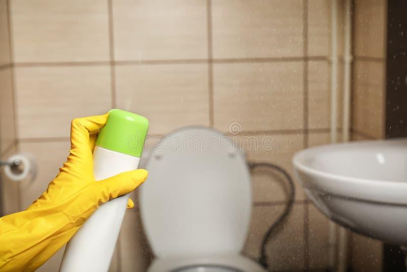 Person spraying air freshener. In bathroom royalty free stock photos