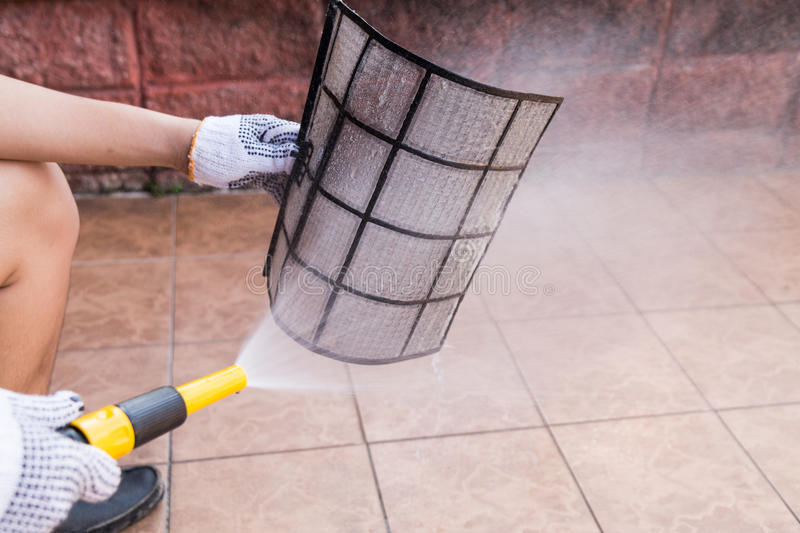 Person spraying water onto air conditioner filter to clean dust stock photos