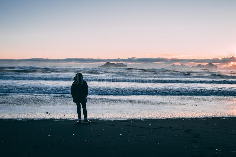 Person Standing on Beach Seashore during Sunset royalty free stock photography