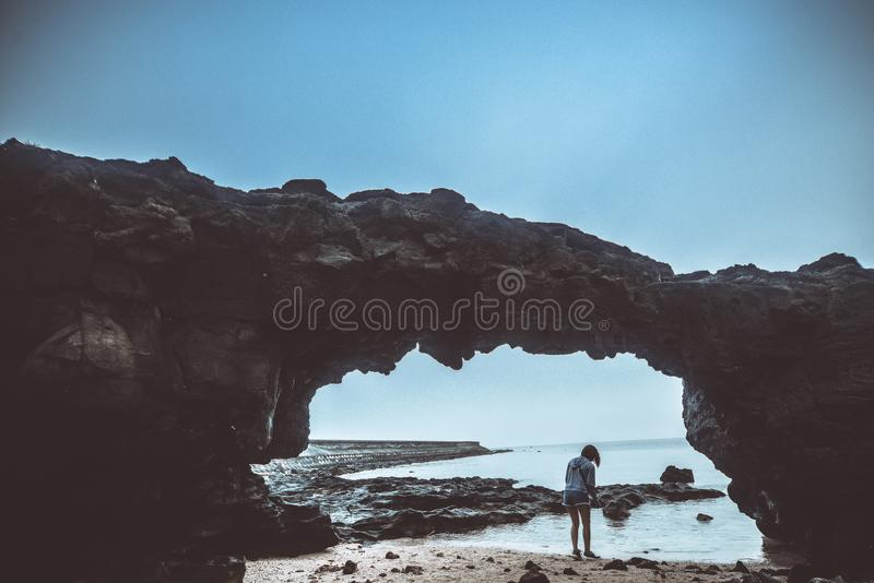 Person Standing on Beach Under Rock stock photos