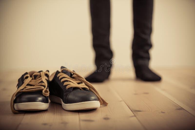 Person Standing Behind Pair de zapatos en el piso de madera foto de archivo