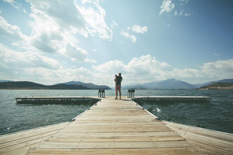 Person Standing on Brown Wooden Dock Under Clue Sky during Daytime royalty free stock photography