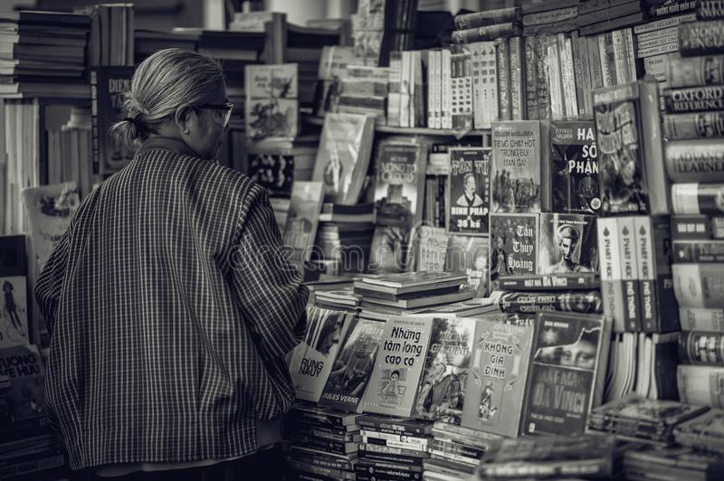 Person Standing in Front of Assorted Books in Gray Scale Photography royalty free stock photography
