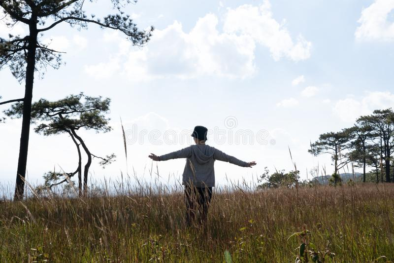 A person standing in large field enjoying the nature under beautiful blue sky stock photography