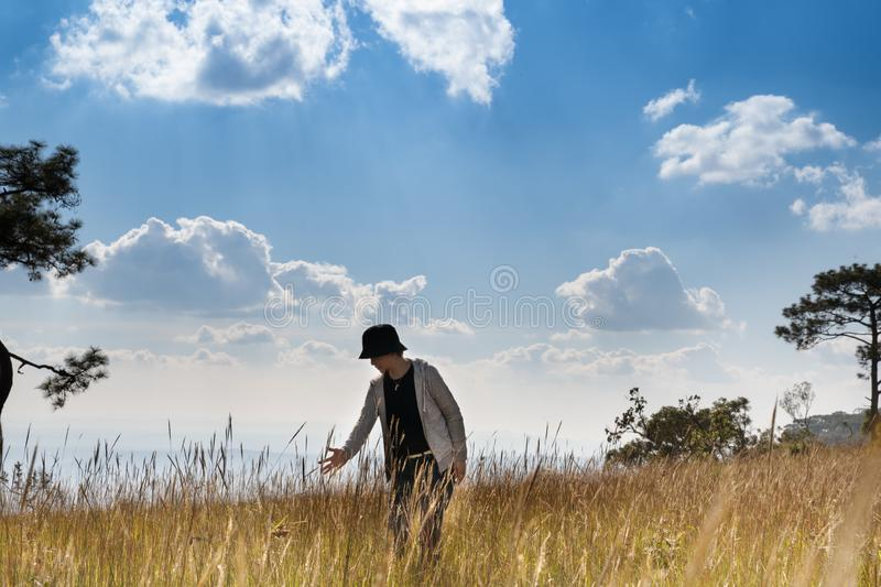 A person standing in large field enjoying the nature under beautiful blue sky royalty free stock photo