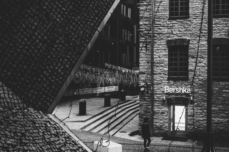 Person Standing Near Bershka Building Grayscale Photography royalty free stock photo