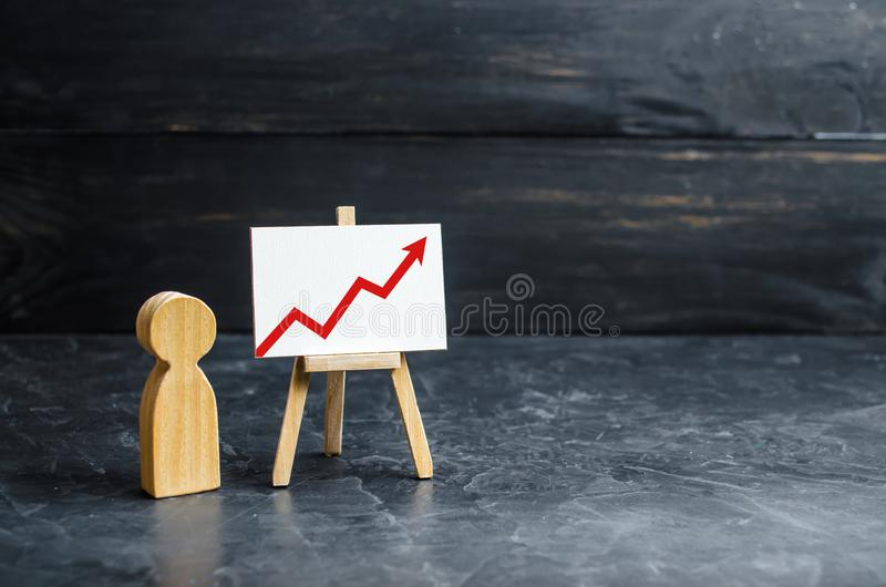 A person is standing near a chart with a red up arrow. Financial success and achievement. Business report and idea. Summarizing. Analysis and market research royalty free stock photo