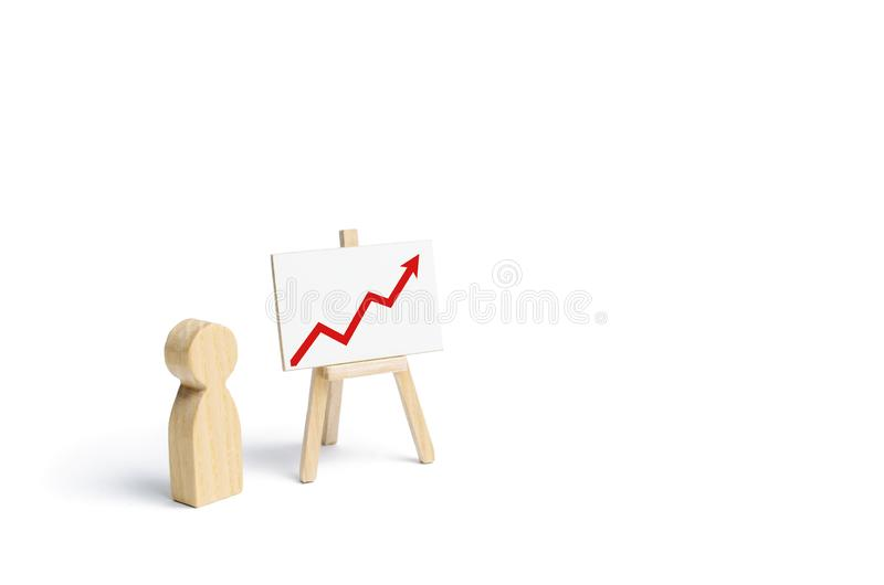 A person is standing near a chart with a red up arrow. Financial success and achievement. Business report and idea. Summarizing. Analysis and market research stock photography