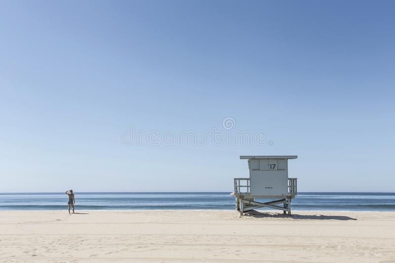 Person Standing Near Life Guard House On Beach Under Blue Clear Skies Free Public Domain Cc0 Image
