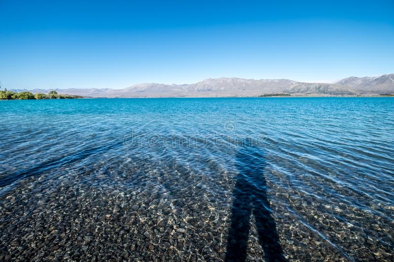 A person standing next to a crystal clear freshwater lake in New Zealand. The day is beautiful. There are clear blue sky, stunning mountains, crystal clear stock image