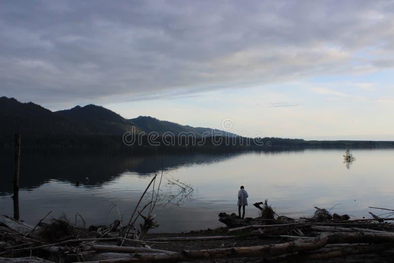 Person Standing op de rand van een meer bij Zonsondergang royalty-vrije stock afbeeldingen