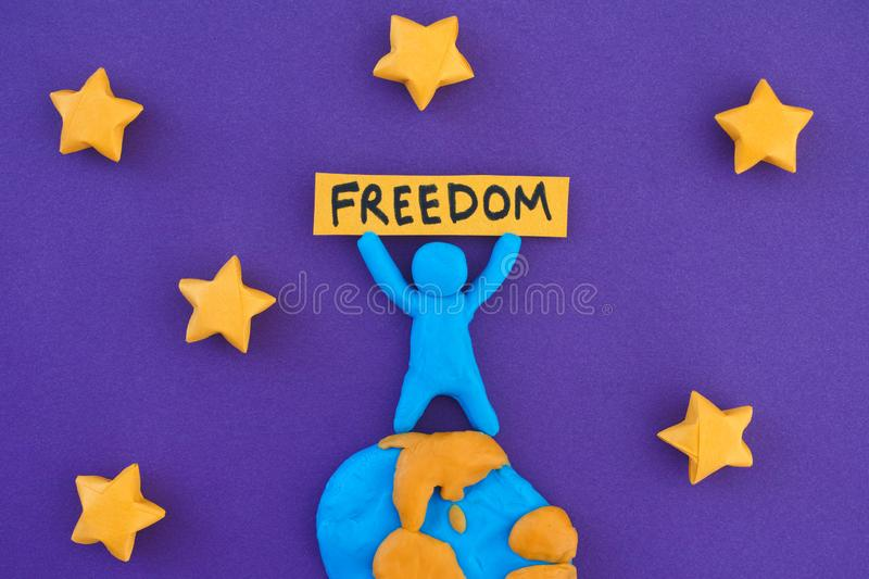 Person standing on planet Earth and holding the word Freedom stock image