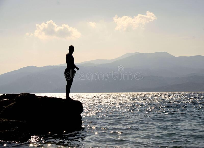 Person Standing On Rock Besides Sea Near Island During Daytime Free Public Domain Cc0 Image