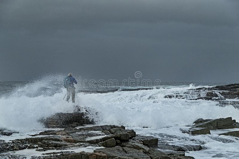 Person standing on the rocky beach in front of the big foamy waves under the cloudy sky stock image