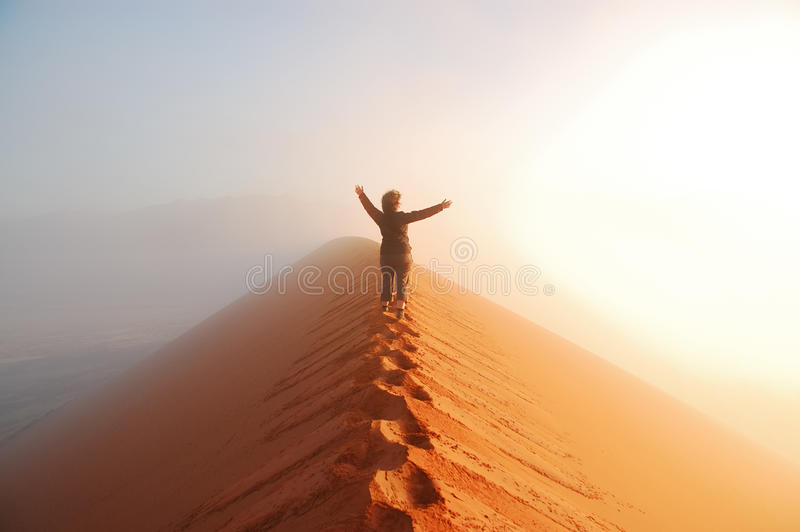 Person standing on top of dune in desert and looking at rising sun in mist with hands up, travel in Africa stock photo