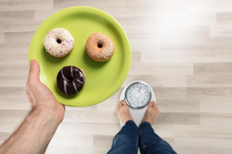 Person Standing On Weighing Machine. High Angle View Of A Person Holding Plates Of Donut Standing On Weighing Machine stock image