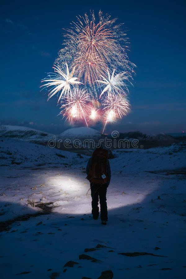 Person Stands on Snow Covered Mountain Looking at Fireworks stock photos